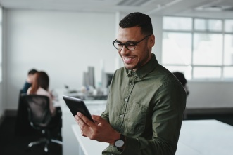 Man Looking at a Tablet and Smiling   Software AG Government Solutions