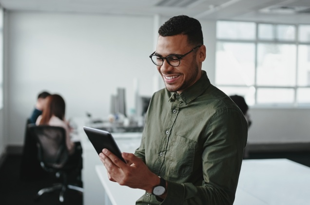 Man Looking at a Tablet and Smiling | Software AG Government Solutions